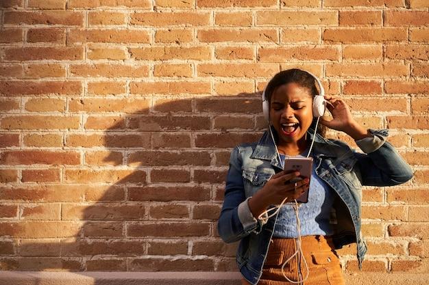 Portret młodej kobiety african american ze słuchawkami do słuchania muzyki