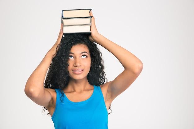 Portret młodej kobiety afro american trzymając książki na głowie i patrząc w górę na białym tle na białej ścianie
