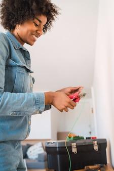 Portret młodej kobiety afro ustalania problemu energii elektrycznej z kablami w nowym domu. koncepcja domu naprawy i renowacji.