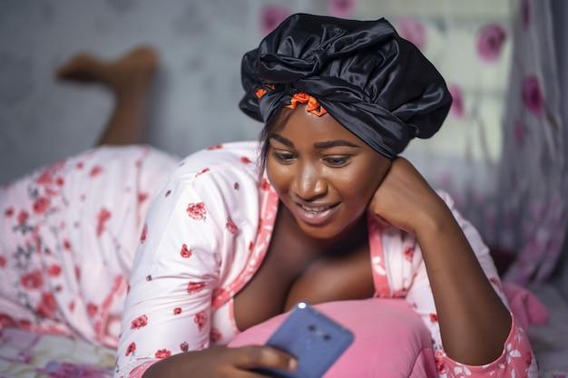 Portret młodej kobiety afroamerykanów w satynowej czapeczce, używając swojego telefonu na łóżku