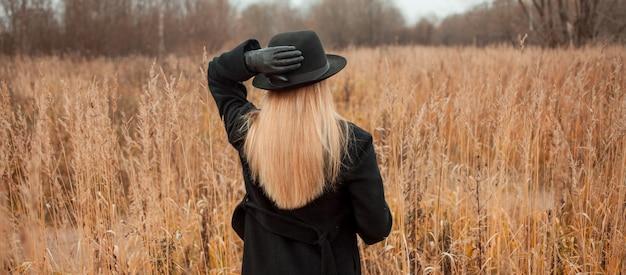 Portret młodej kobiety atrakcyjne w czarny płaszcz i kapelusz