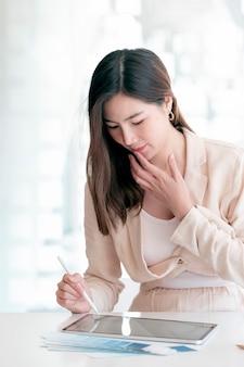 Portret młodej kobiety azjatyckie pracy na tablecie siedząc przy biurku w nowoczesnym biurze.