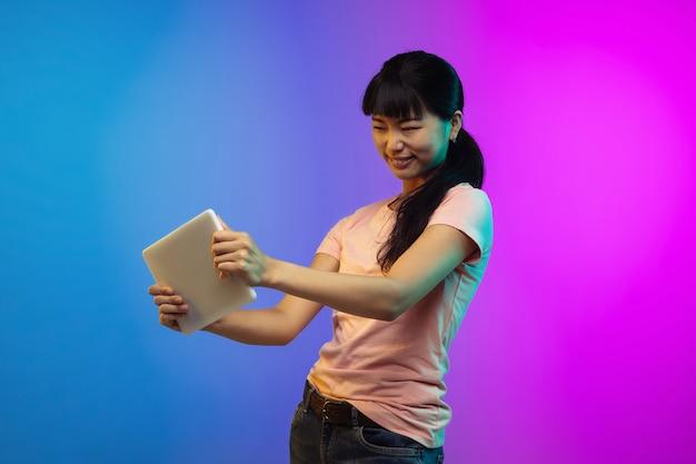 Portret młodej kobiety azjatyckiej na gradientowym tle studio w neonowym