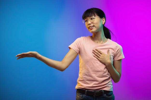 Portret młodej kobiety azjatyckiej na ścianie gradientowej w studio