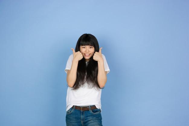 Portret młodej kobiety azji na białym tle na niebieskiej przestrzeni studio
