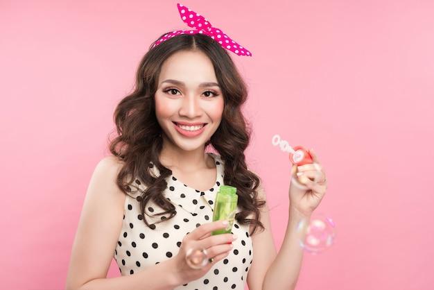 Portret młodej kobiety bawi się baniek mydlanych na różowym tle.