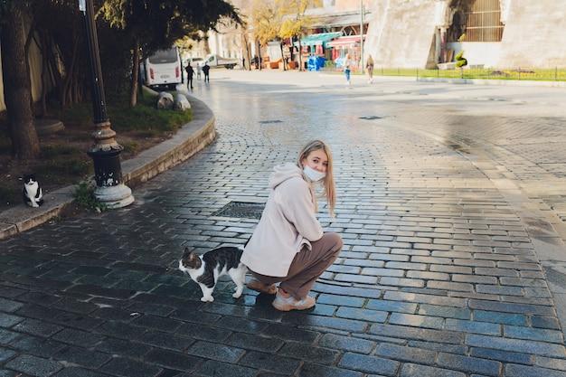 Portret młodej kobiety bawi się kotem na ulicy miasta.