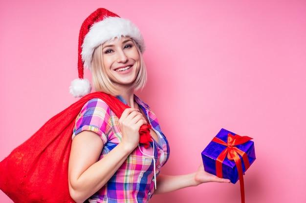 Portret młodej kobiety beautyful blond zdumiony z prezentem pudełko boże narodzenie na czerwonym tle. pani w kraciastej koszuli i mikołaj trzymają w studio torbę pełną prezentów na różowym tle.