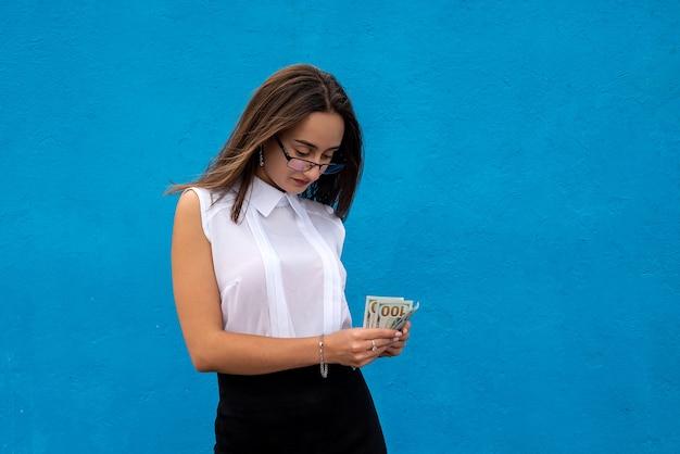 Portret młodej kobiety biznesu, która odniosła sukces, trzyma dużo pieniędzy dolarowych na niebieskim tle