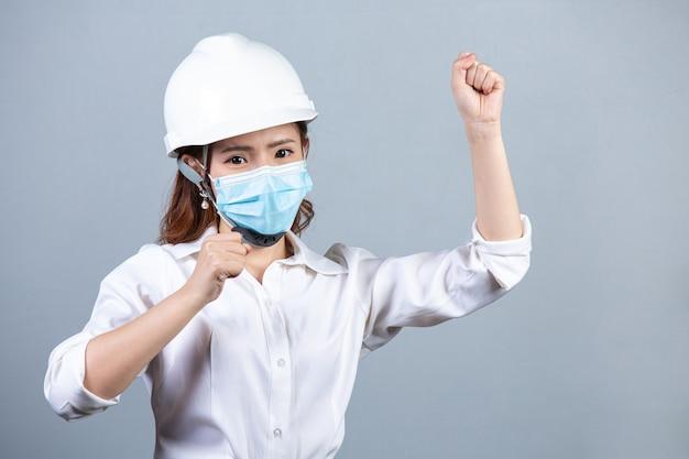 Portret młodej kobiety biznesu piękne noszenie maski na szarej powierzchni