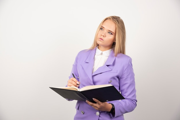 Portret młodej kobiety biznesu stojąc i trzymając schowek.