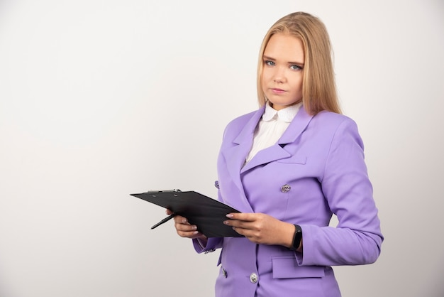 Portret młodej kobiety biznesu, stojąc i trzymając schowek.