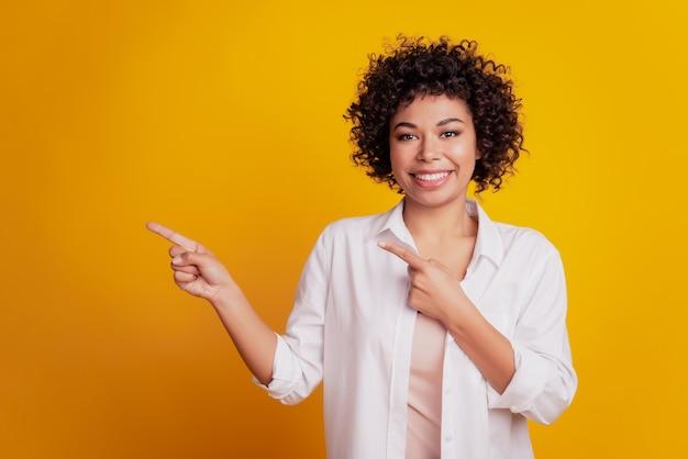 Portret młodej kobiety biznesu wskazując palcami pustą przestrzeń doradza nowość na żółtym tle