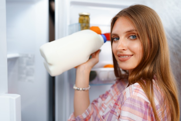 Portret młodej kobiety blondynka, biorąc jedzenie z jej lodówki