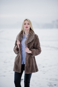 Portret młodej kobiety blondynka elegancji w futrze, mglista rzeka na lodzie zimowym.