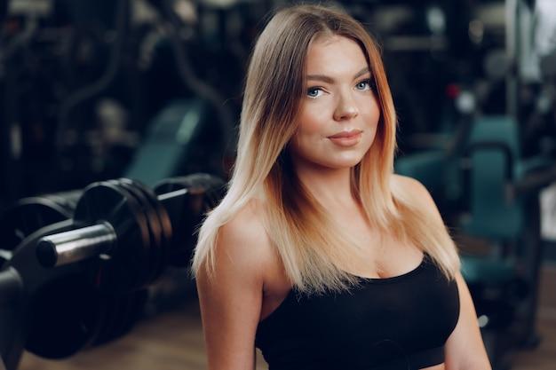 Portret młodej kobiety blondynka sprawny w czarny sportowy stanik