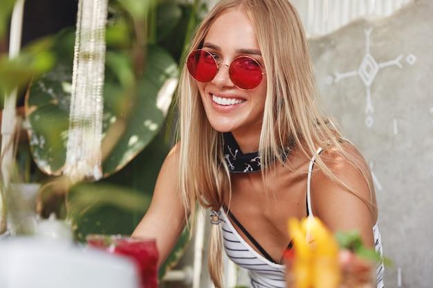 Portret młodej kobiety blondynka w paski t-shirt i chustka z czerwonymi okularami przeciwsłonecznymi