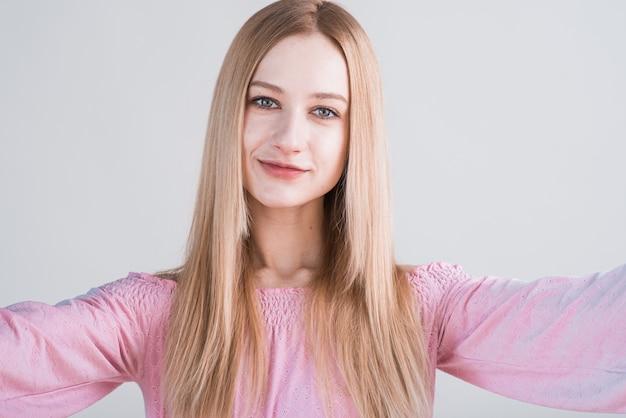 Portret młodej kobiety blondynka z gestem uścisk w studio na białym tle