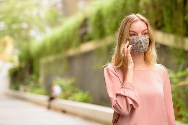Portret młodej kobiety blondynka z maską do ochrony przed wybuchem wirusa koronowego na ulicach miasta z przyrodą na zewnątrz