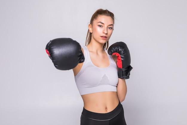 Portret młodej kobiety bokser rzuca cios z przodu podczas ćwiczeń
