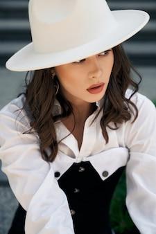 Portret młodej kobiety brunetka na sobie białą koszulę, kapelusz i czarny gorset na zewnątrz. modelki z idealnym makijażem pozowanie na ulicy miasta, szare schody. koncepcja mody.