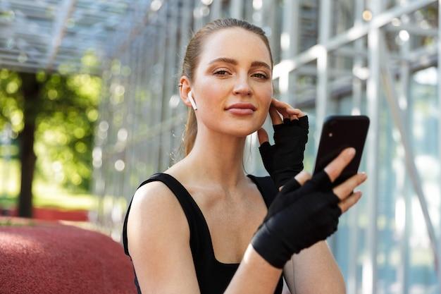 Portret młodej kobiety brunetka noszącej słuchawki douszne trzymającej smartfon i odpoczywającej po treningu z poziomym metalowym drążkiem na boisku sportowym w zielonym parku