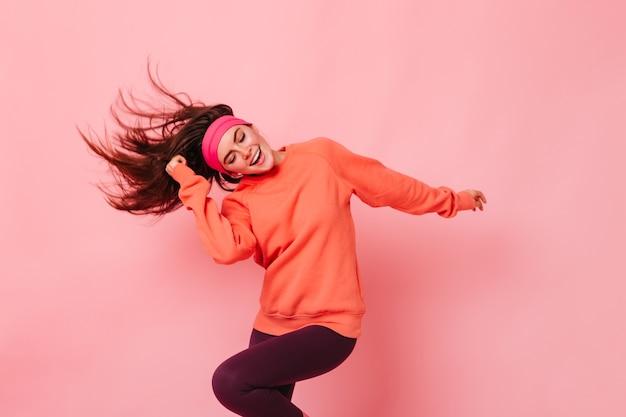 Portret młodej kobiety brunetka robi fitness na różowej ścianie
