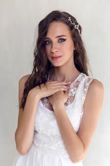 Portret młodej kobiety brunetka stojącej w długiej białej sukni na białej ścianie