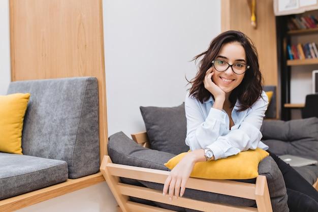 Portret młodej kobiety brunetka w czarnych okularach chłodzenie na kanapie w nowoczesnym mieszkaniu. komfortowy, wesoły nastrój, uśmiechnięty
