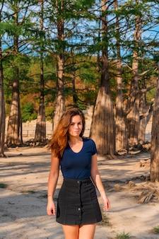 Portret młodej kobiety brunetka w gaju cyprysowym rosnącym w jeziorze sukko