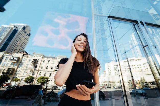Portret młodej kobiety brunetka ze słuchawkami i uśmiechnięty podczas chodzenia