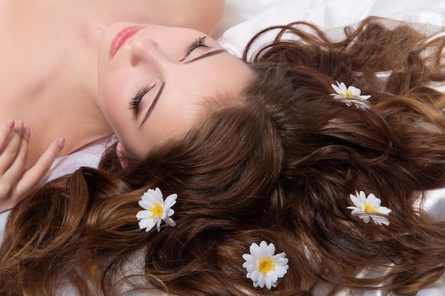 Portret młodej kobiety brunettete z kwiatami rumianku we włosach