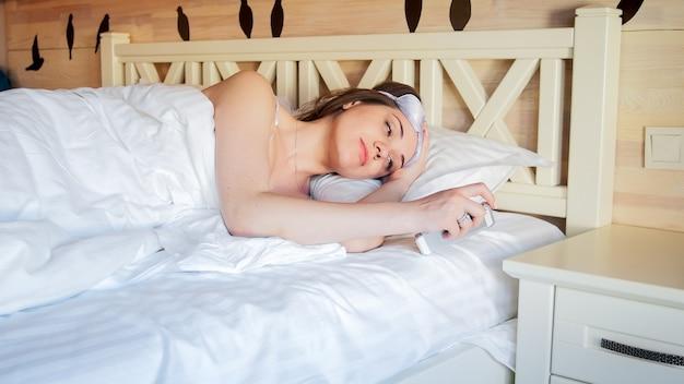 Portret młodej kobiety budzącej się patrząc na smartfona i zdejmującej maskę do spania