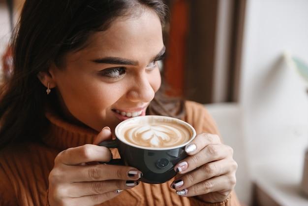Portret młodej kobiety całkiem piękne siedzi w kawiarni w pomieszczeniu picia kawy.