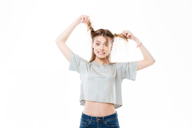 Portret młodej kobiety ciągnięcie włosów i patrząc na kamery