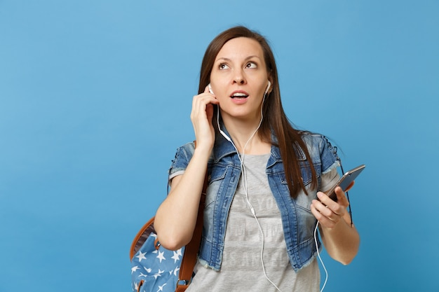 Portret młodej kobiety ciekawa studentka z plecakiem i słuchawkami słuchania muzyki trzymając telefon komórkowy patrząc na białym tle na niebieskim tle. edukacja na uniwersytecie. skopiuj miejsce na reklamę.