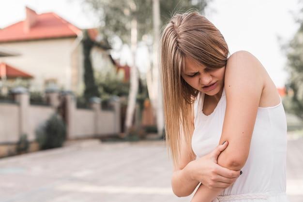 Portret młodej kobiety cierpi na łokieć