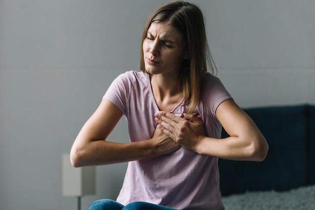 Portret młodej kobiety cierpiące na ból w klatce piersiowej