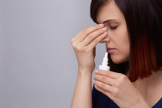 Portret młodej kobiety cierpiącej na katar i alergię, trzymającej palce za nos i przygotowującej się do użycia aerozolu do nosa.