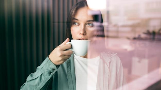 Portret młodej kobiety, ciesząc się kawą