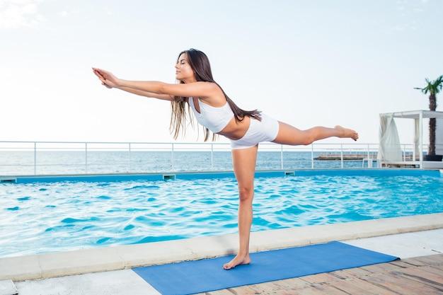 Portret młodej kobiety ćwiczeń rozciągających na świeżym powietrzu w godzinach porannych