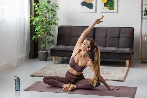 Portret młodej kobiety ćwiczeń w domu na macie