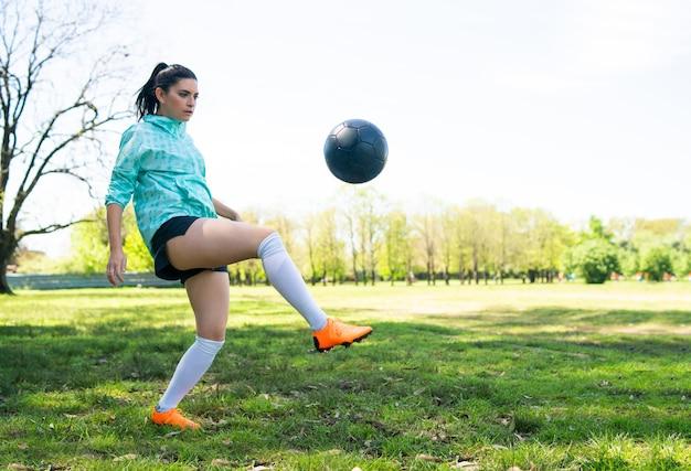 Portret młodej kobiety ćwiczyć umiejętności piłki nożnej i robić sztuczki z piłką nożną. piłkarz żonglujący piłką. koncepcja sportu.