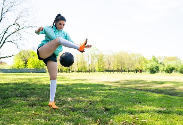 Portret młodej kobiety ćwiczyć umiejętności piłki nożnej i robić sztuczki z piłką nożną.
