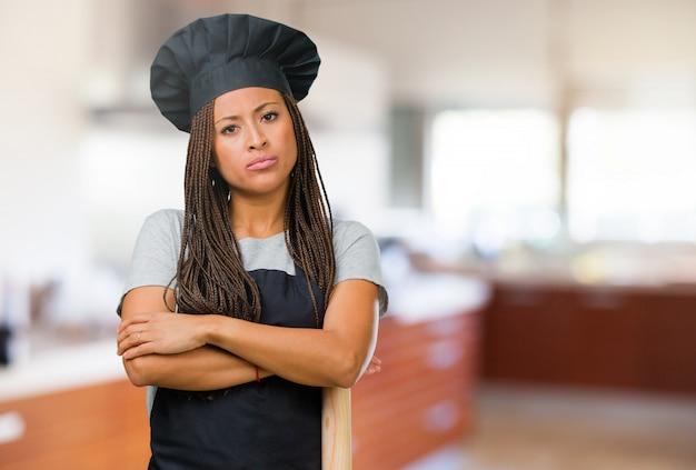 Portret młodej kobiety czarny piekarz bardzo zły i zdenerwowany, bardzo spięty, krzyczy wściekły, negatywny i szalony