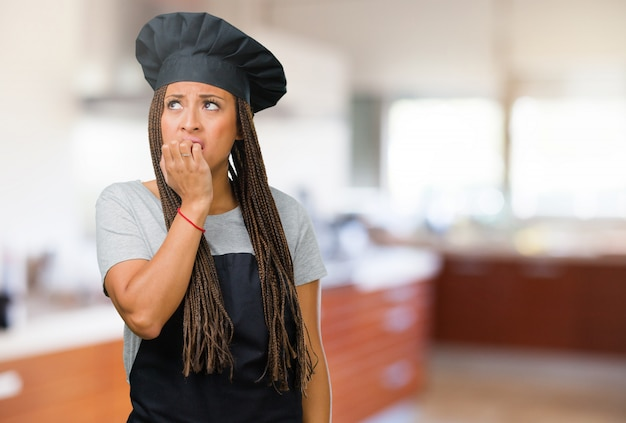 Portret młodej kobiety czarny piekarz obgryzanie paznokci, nerwowy i bardzo niespokojny i przerażony na przyszłość, czuje panikę i stres