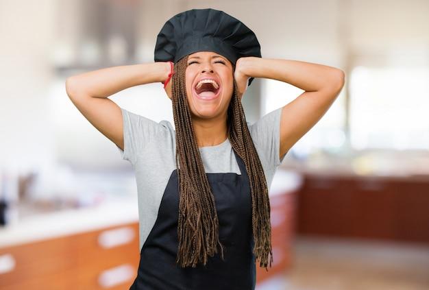 Portret młodej kobiety czarny piekarz szalony i zrozpaczony, krzycząc z kontroli