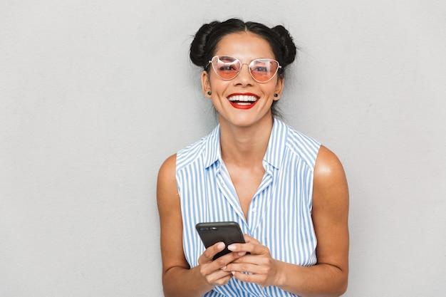 Portret młodej kobiety delighed w okularach przeciwsłonecznych na białym tle, przy użyciu telefonu komórkowego
