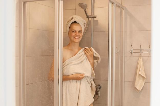 Portret młodej kobiety dorosłej wychodzącej spod prysznica, stojącej i patrzącej na kamerę z szczęśliwym wyrazem twarzy, owiniętej jej ciało i włosy białymi ręcznikami.