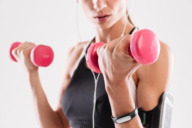 Portret młodej kobiety fitness robi ćwiczenia z hantlami